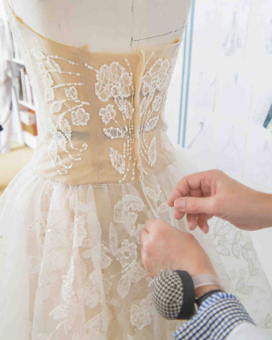 Varrónő varrja az esküvői ruhát.