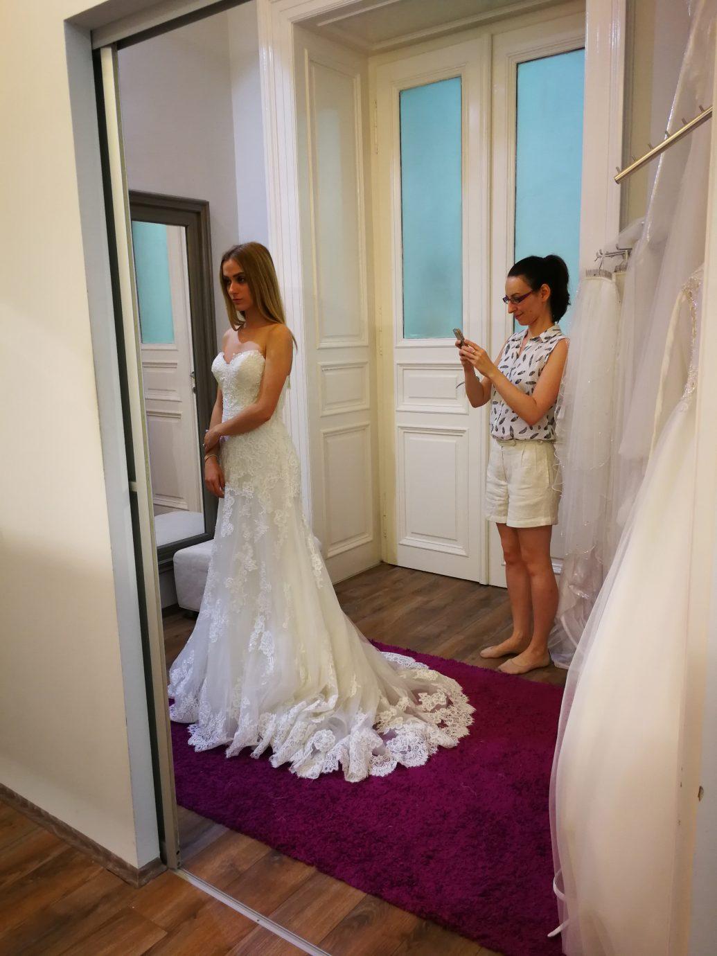 A-vonalú esküvői ruha, melyet a menyasszony kísérőjével próbál az Igen Szalonban.
